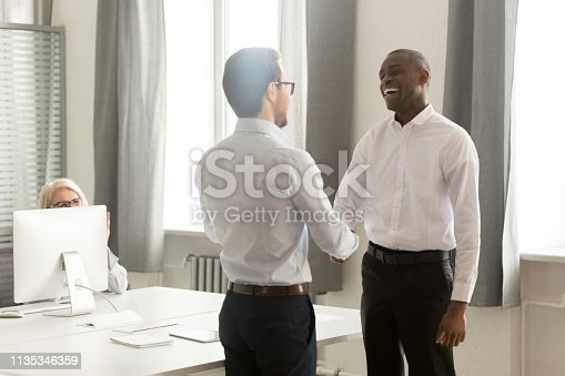 istock Happy african male employee getting rewarded appreciated promoted by boss 1135346359