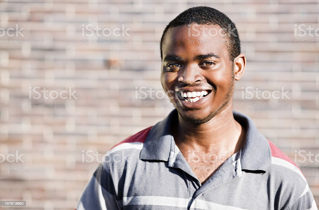 Happy African man against brick wall stock photo