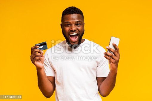 1173546354 istock photo Happy african man holding credit card and cellphone in his hands 1171091214