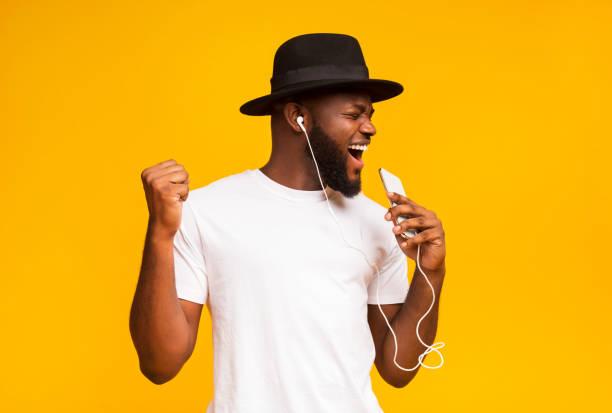 szczęśliwy afrykański człowiek w kapeluszu śpiewa do smartfona jak mikrofon - muzyka zdjęcia i obrazy z banku zdjęć