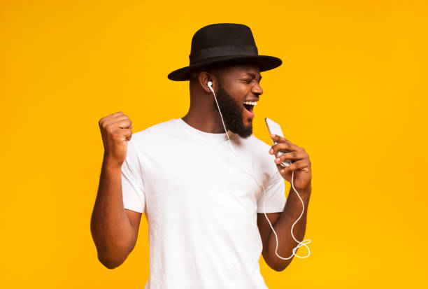 Happy african man in hat singing into smartphone like microphone Emotional african guy in black hat singing into smartphone like microphone and listening to music via earphones, yellow background with free space singing stock pictures, royalty-free photos & images