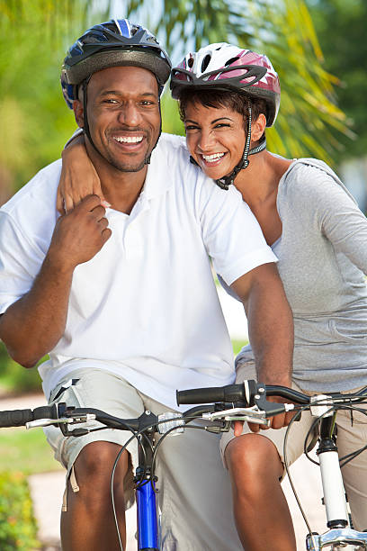 Happy African Man & Woman Couple Riding Bike Smiling stock photo