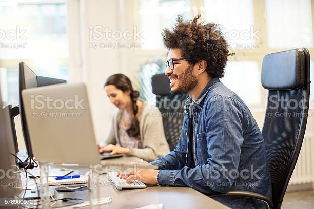 Happy african man working at his desk picture id576900972?b=1&k=6&m=576900972&s=612x612&h=c5bn99ax6v5au3qfnbpvlj6s3prnfo2 g5fvgaqr5we=