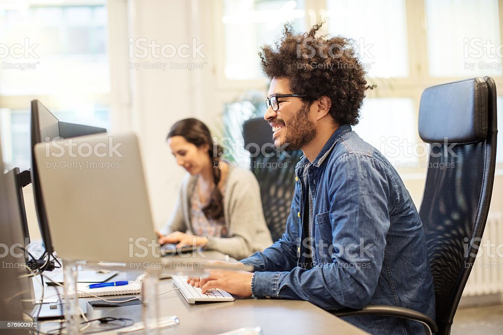 Happy african man working at his desk stock photo