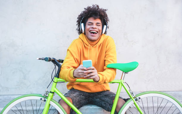 Happy african millennial guy listening music playlist with smartphone app outdoor - Young man having fun with technology trends - Tech, generation z and stylish concept - Focus on face stock photo