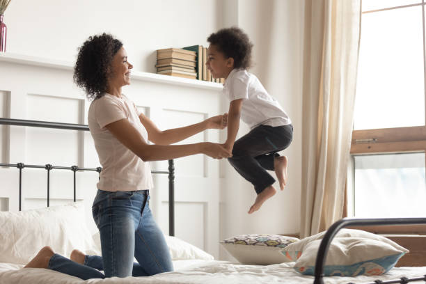 Happy african mom playing with kid boy jumping on bed Happy african american family loving single mom holding hands of cute little kid boy laugh jumping on bed, young mixed race mother having fun playing funny active game with small child son in bedroom bed furniture stock pictures, royalty-free photos & images