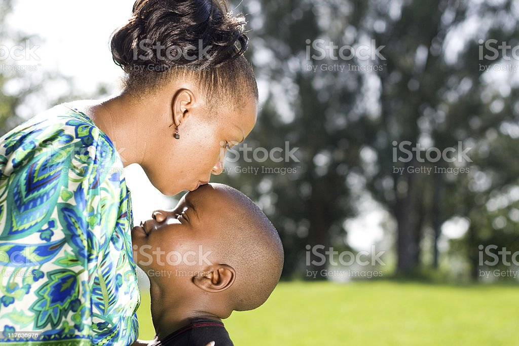 happy african mother kissing son stock photo