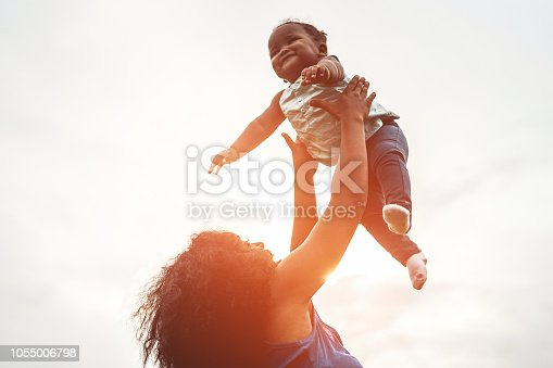 Happy african mother playing with her daughter outdoor - Afro mum and child having fun together - Family, happiness and love concept - Soft focus on woman face