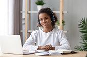 istock Happy african schoolgirl wearing headphones e-learning using computer 1133045055