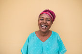 Happy african senior woman laughing and look in camera - Portrait of real and authentic person wearing traditional dress