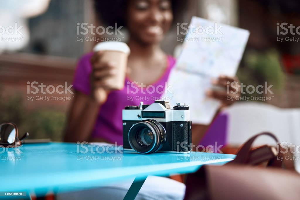 Cropped portrait of smiling afro-american female looking on map while...