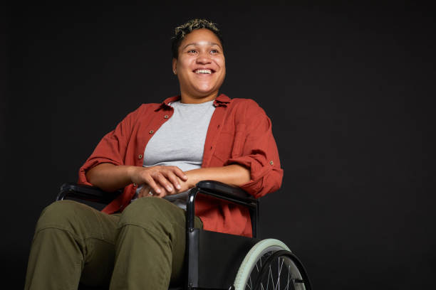 Happy African woman in wheelchair Young African woman with disabilities sitting in wheelchair and smiling isolated on black background paraplegic stock pictures, royalty-free photos & images