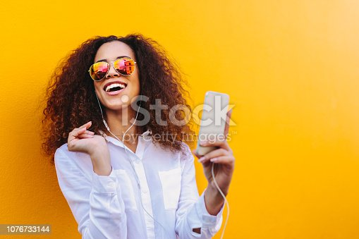 Happy young african woman listening to music on earphones using a mobile phone. Girl with curly hair wearing sunglasses against yellow wall enjoying listening songs on mobile phone.