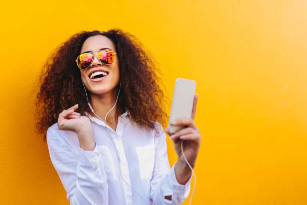 mulher africana feliz ouvindo música - lifestyle color background - fotografias e filmes do acervo