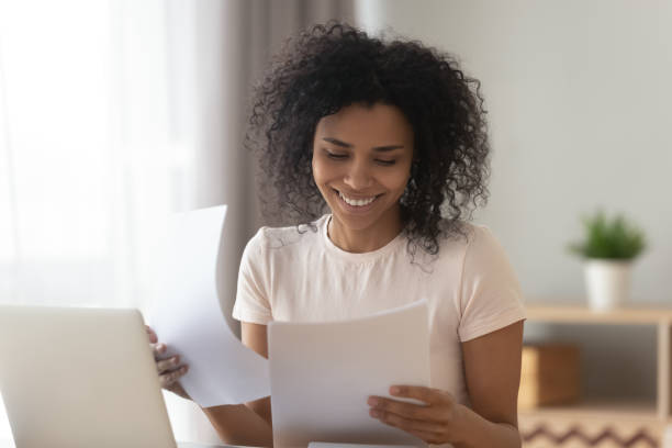 Happy african woman sit at table reading paper checking bills Happy young african american woman sit at table reading good news in paper letter checking domestic bills, smiling black holding documents doing paperwork work or study sit at home office desk refund stock pictures, royalty-free photos & images
