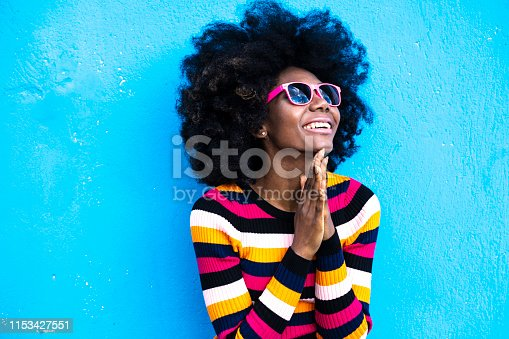 African woman standing in front of color background.