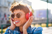 Young smiling african woman relaxing and listening music with headphones at sunset. Brazilian smiling girl listening songs via wireless headphones on the street. Closeup face of teen wearing sunglasses and keeps the rhythm of the song.