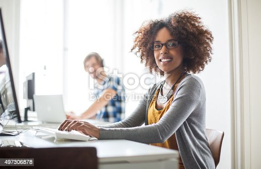 istock Happy african woman working at her desk 497306878