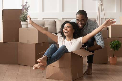 istock Happy african young couple riding in box on moving day 1158481676