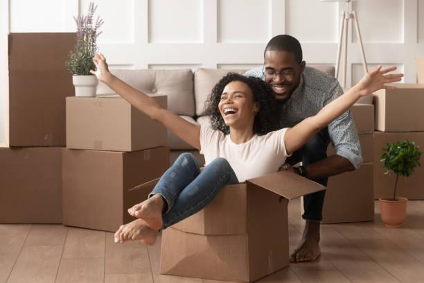 glückliches afrikanisches junges paar reitet in box am umzugsfreudigen tag - eigenheim stock-fotos und bilder