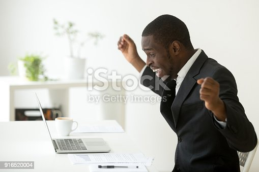 istock Happy african-american businessman celebrating success online win looking at laptop 916520004