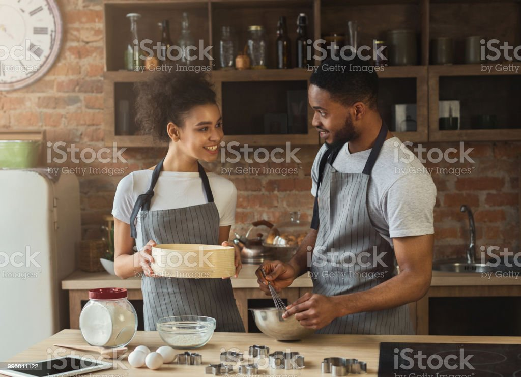 Happy african-american couple cooking cookies together stock photo