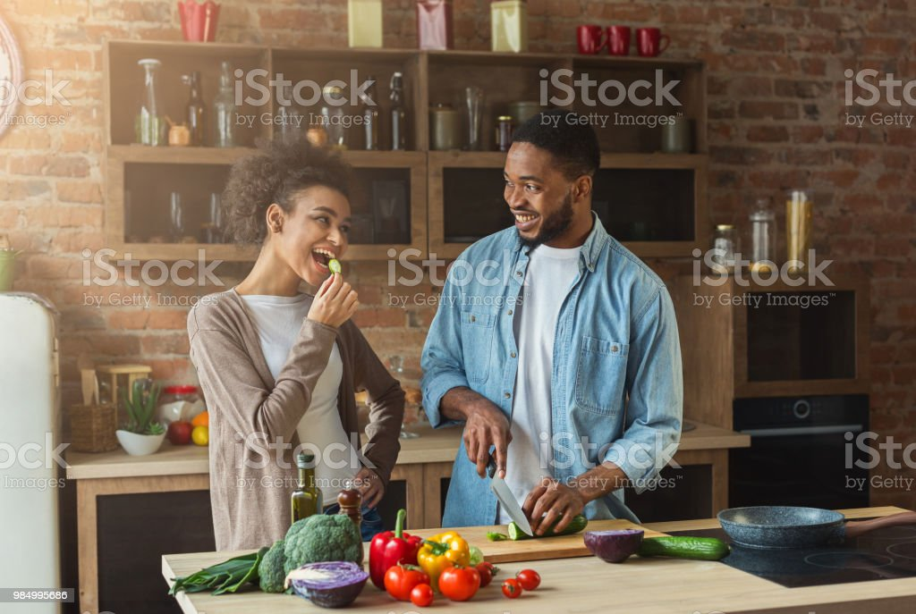 Happy african-american couple cooking in loft kitchen stock photo