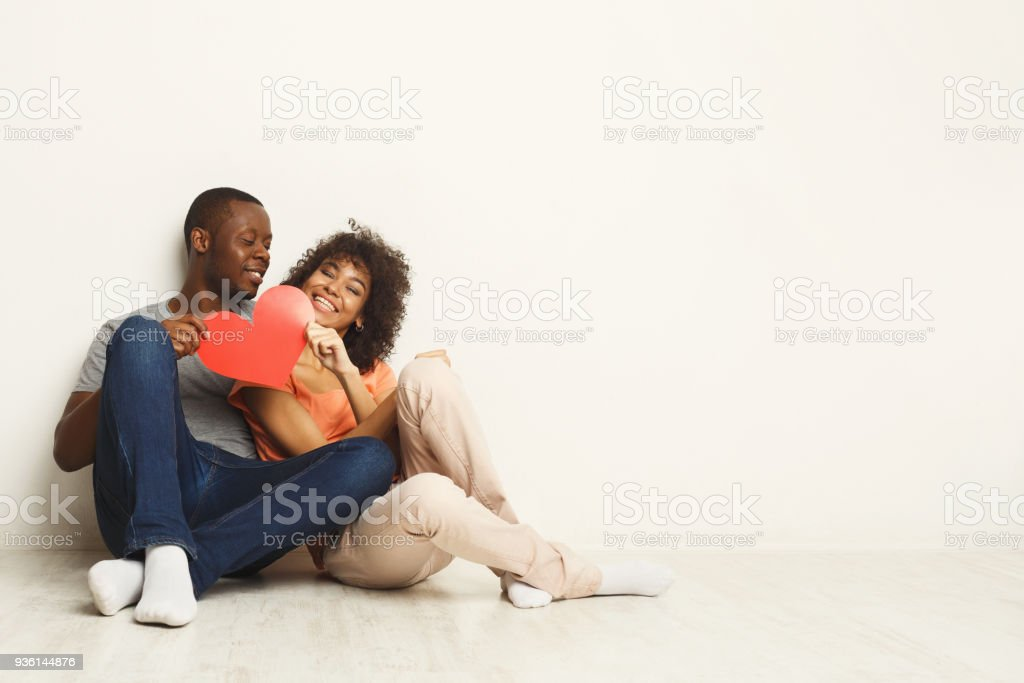 Happy african-american couple holding paper heart Young happy african-american couple in love holding red paper heart, sitting on floor of new flat, copy space. Family and valentine day concept, isolated Adult Stock Photo