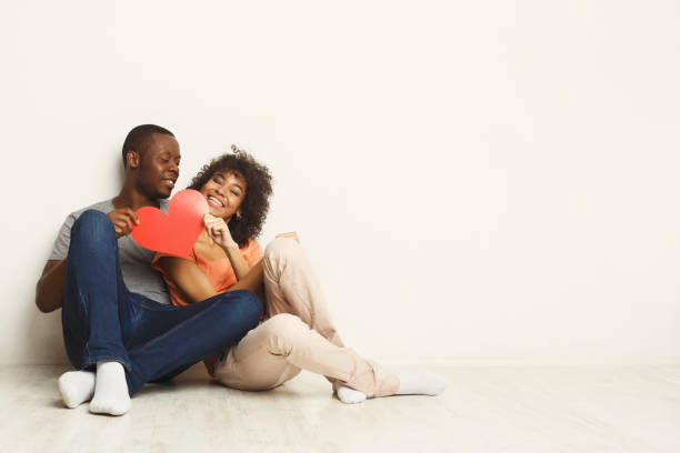 Happy african-american couple holding paper heart Young happy african-american couple in love holding red paper heart, sitting on floor of new flat, copy space. Family and valentine day concept, isolated two parents stock pictures, royalty-free photos & images