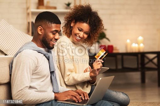 Online shopping. Happy african-american couple looking at laptop and buying with credit card at home, free space