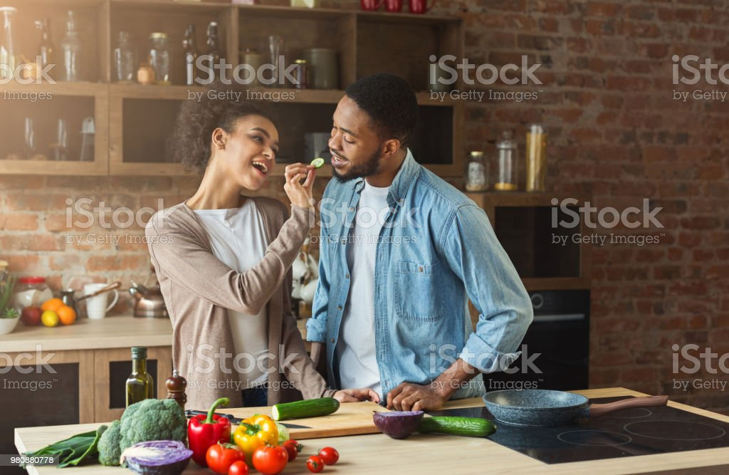 Happy african-american couple preparing dinner stock photo