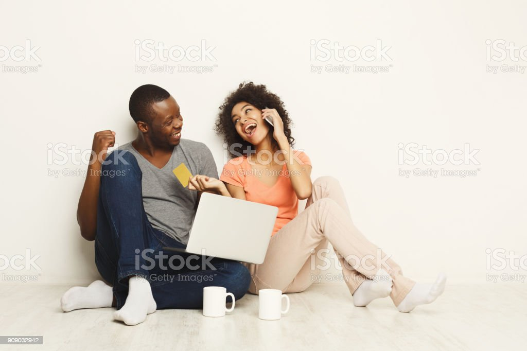 Happy african-american couple shopping online on laptop stock photo