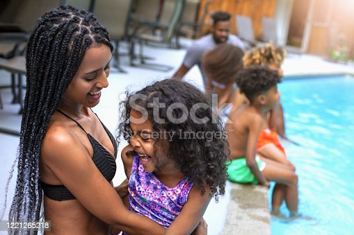 Happy African-American family on vacation spending time together by swimming pool