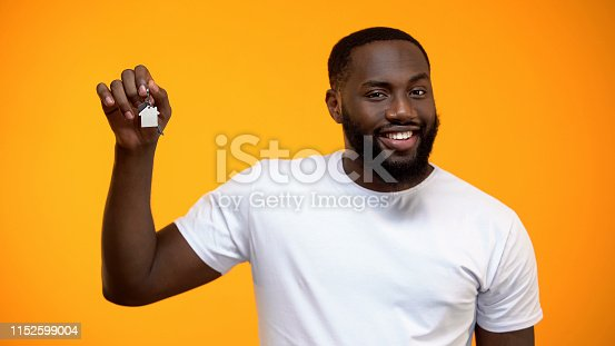 istock Happy African-American man holding house keys, real estate purchase, mortgage 1152599004