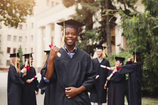 Glücklicher afrikanisch-amerikanischer Mann am graduierungstag seiner – Foto