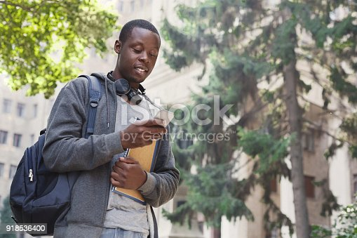 istock Happy african-american student texting in university campus 918536400