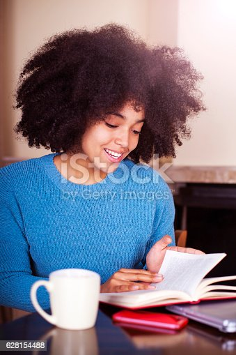 istock Happy african-american young woman reading the book at home 628154488