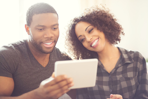 Happy Afro American Couple Using A Digital Tablet At Home Stock Photo - Download Image Now