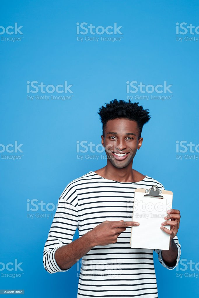 Happy afro american guy holding clipboard Happy afro american young man wearing striped top holding clipboard in hand, pointing at the copy space and smiling at camera. Studio portrait, blue background. Adult Stock Photo