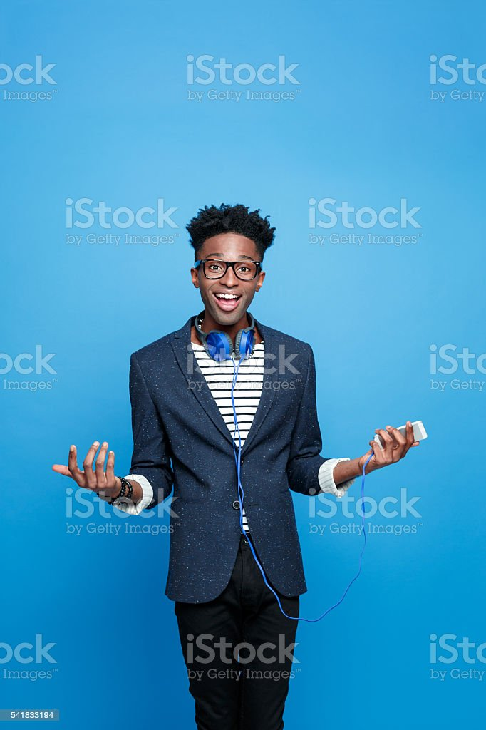 Happy afro american guy holding smart phone in hand Excited afro american young man wearing striped top, navy blue jacket, nerd glasses and headphone, holding smart phone in hand, laughing at camera. Studio portrait, blue background. Adult Stock Photo