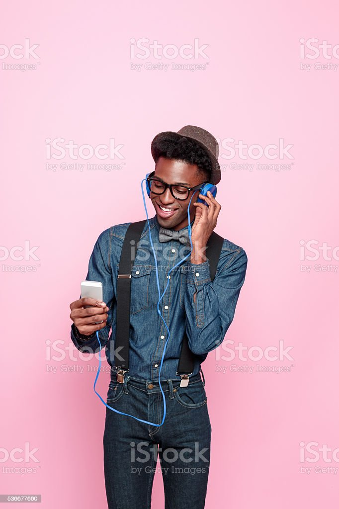 Happy afro american guy listen to music using smart phone stock photo