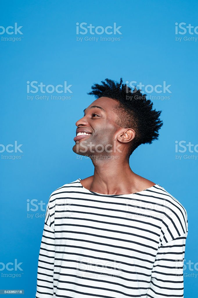 Happy afro american guy Side view of happy afro american young man wearing striped top. Studio portrait, blue background. Adult Stock Photo