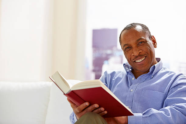 Happy afro American guy reading a book stock photo
