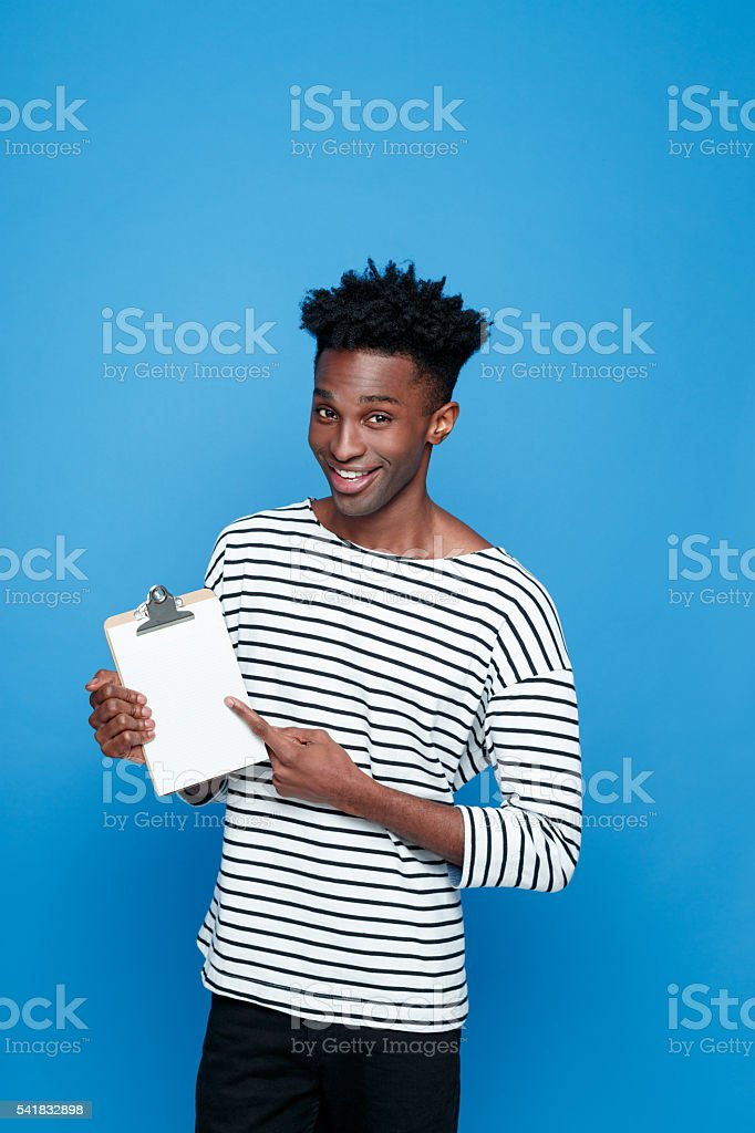 Happy afro american holding clipboard Happy afro american young man wearing striped top holding clipboard in hand, pointing at the copy space and smiling at camera. Studio portrait, blue background. Adult Stock Photo