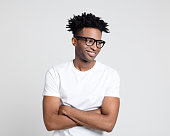Portrait of happy afro american guy with nerd eyeglasses. Man wearing white t-shirt looking away with arms crossed.