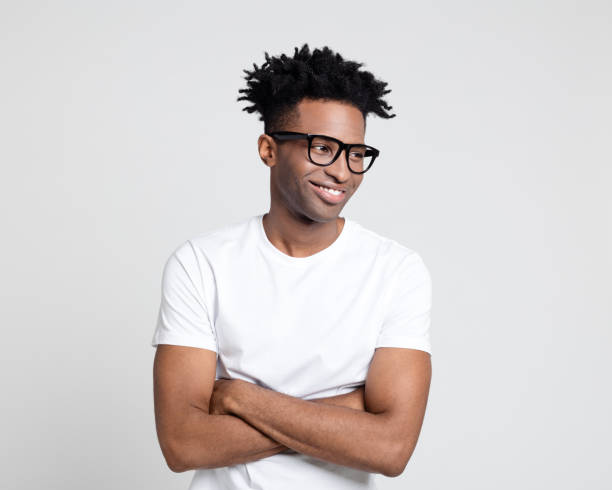 Happy afro american man with nerd eyeglasses looking away Portrait of happy afro american guy with nerd eyeglasses. Man wearing white t-shirt looking away with arms crossed. looking away stock pictures, royalty-free photos & images