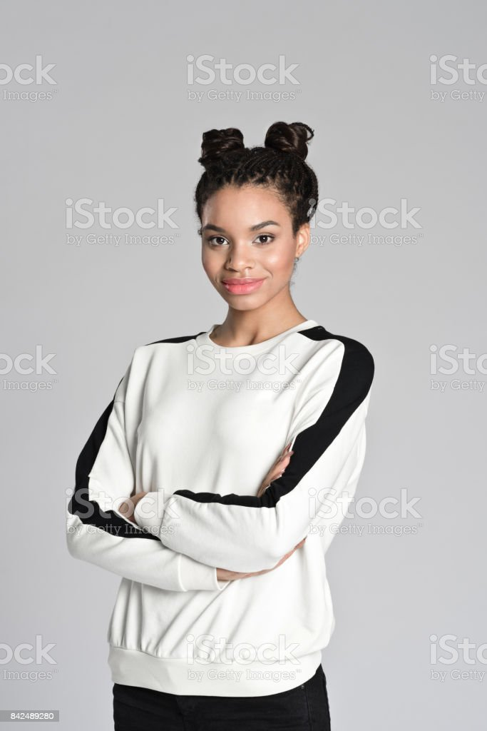 Happy afro american teen girl Studio portrait of smiling afro american teen female student standing with arms crossed. Studio shot, grey background. 16-17 Years Stock Photo