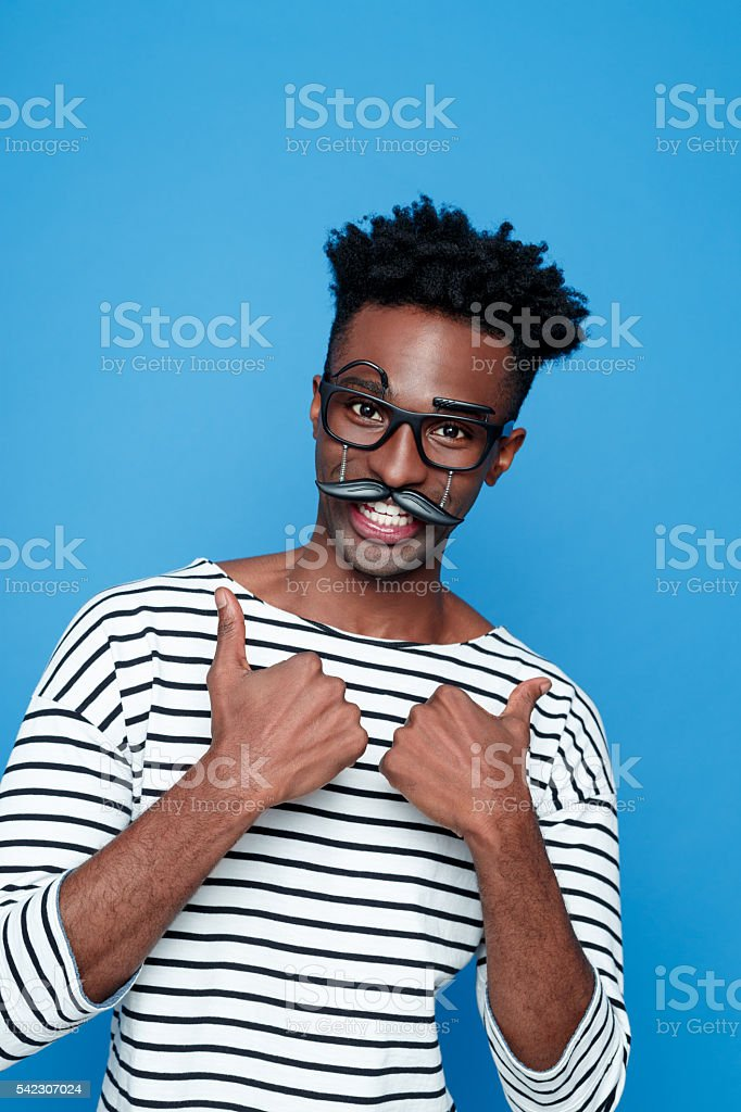 Happy afro american young man wearing funny glasses Portrait of happy afro american guy wearing striped long sleeved t-shirt and funny glasses, laughing at camera with thumbs up. Studio shot, blue background.  Adult Stock Photo