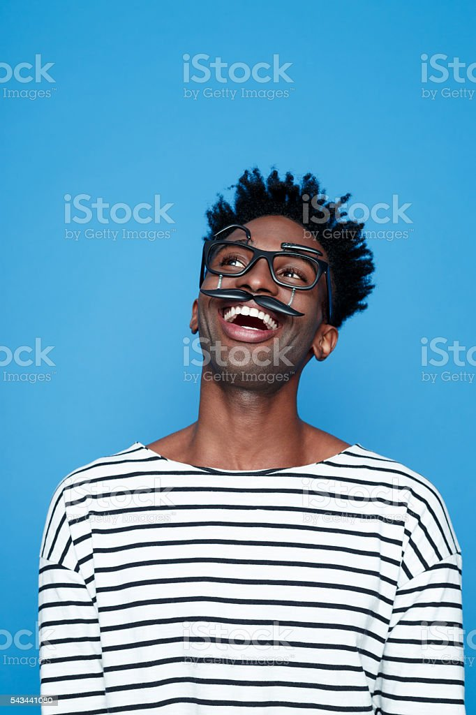 Happy afro american young man wearing funny glasses Portrait of happy afro american guy wearing striped long sleeved t-shirt and funny glasses, laughing. Studio shot, blue background.  Adult Stock Photo