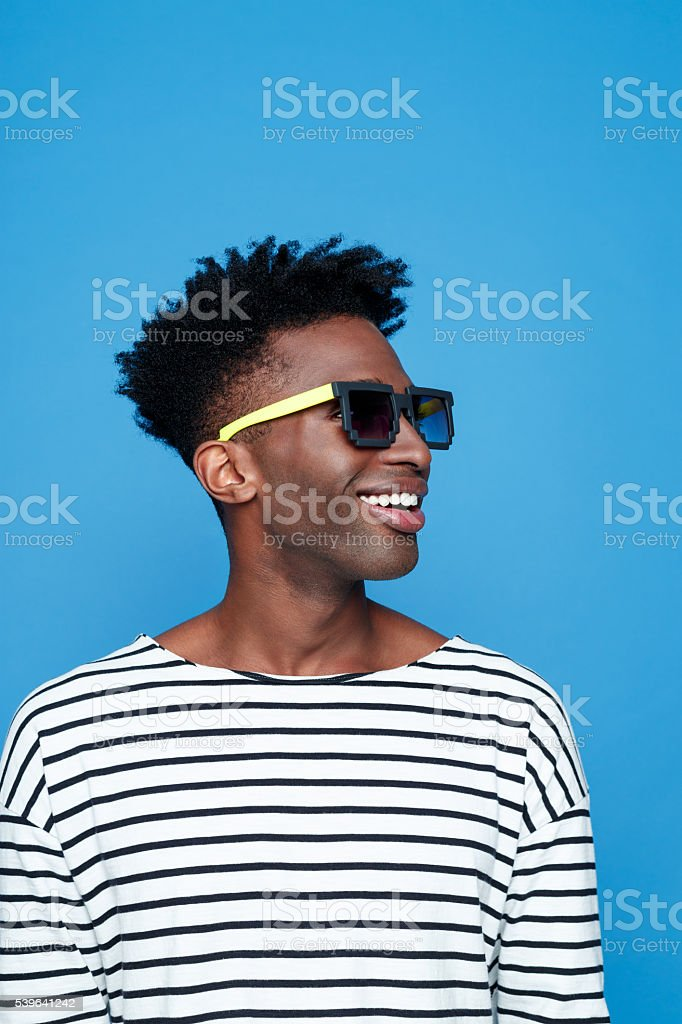 Happy afro american young man wearing sunglasses Portrait of happy afro american guy wearing striped long sleeved t-shirt, wearing sunglasses. Studio shot, blue background.  Adult Stock Photo